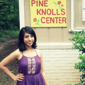Meera Jagannathan posing in front of Pine Knolls Center sign