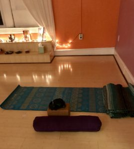 Yoga mat on the ground in a candle-lit room