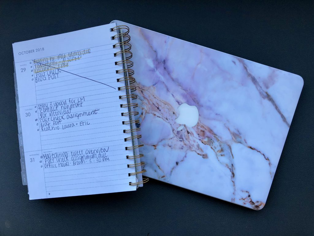 Picture of daily planner and macbook laptop.