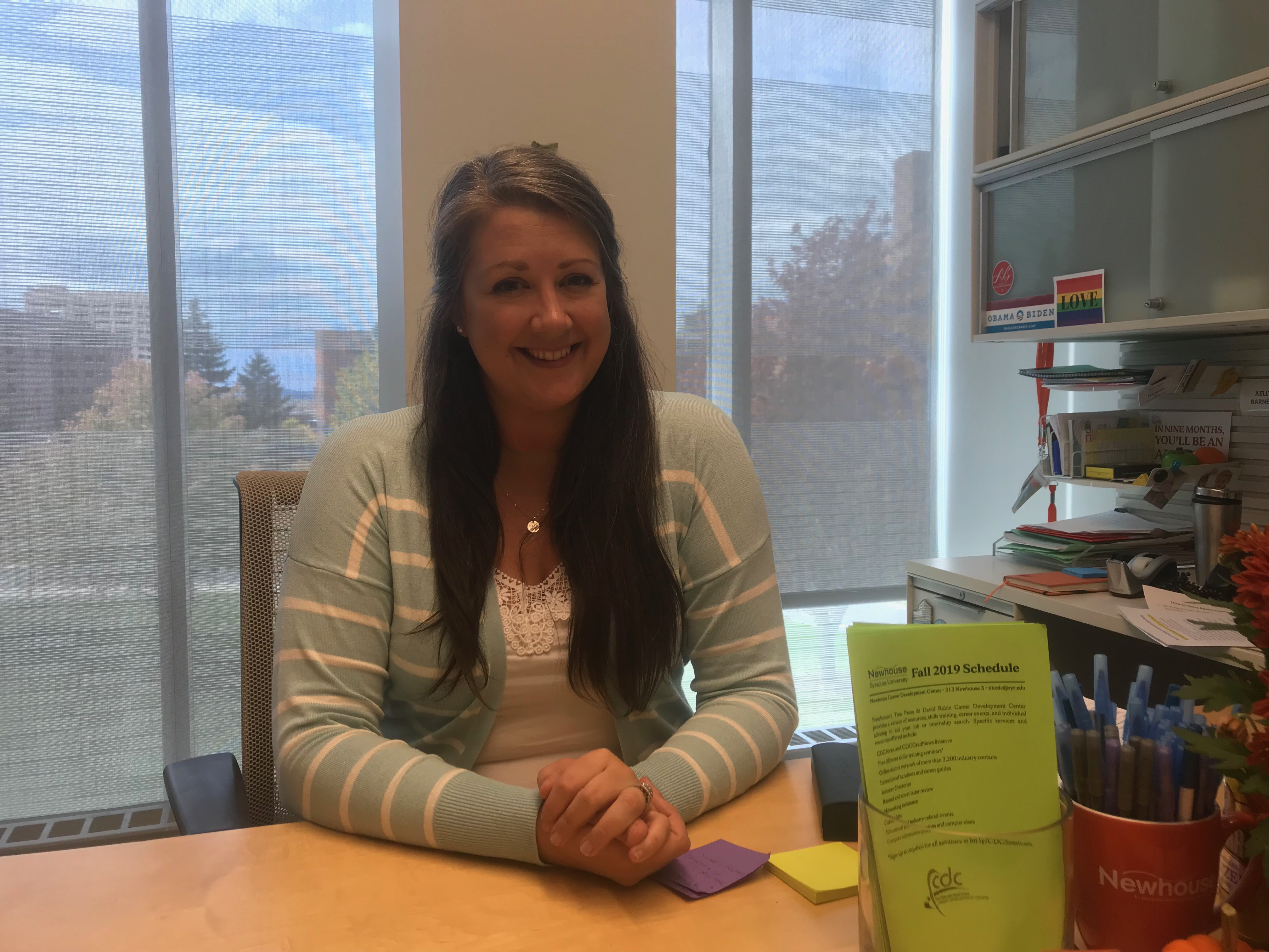 Kelly sits at desk