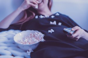 Woman eating popcorn and holding television remote.